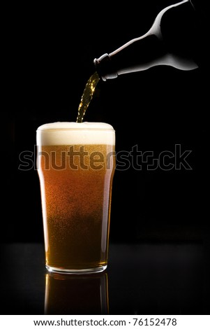 Beer being poured from a beer bottle - stock photo