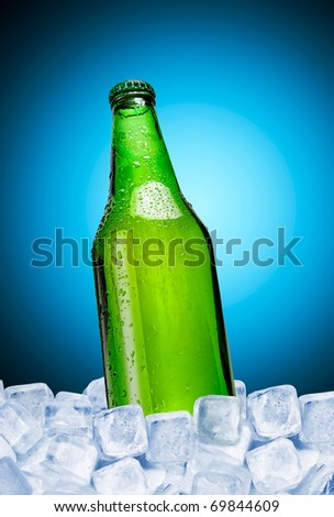 Beer bottle in ice over blue background - stock photo