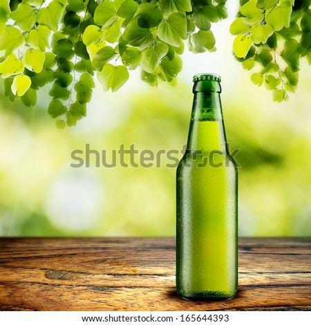 Beer Bottle on wood table with summer scene background - stock photo