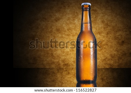 Beer bottle on yellow wooden background - stock photo