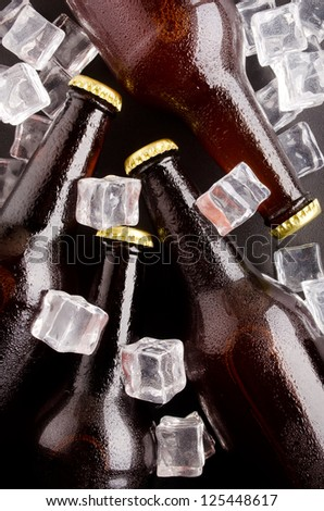 Beer bottles cooled in ice cubes. - stock photo