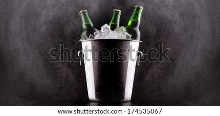 Beer bottles in ice bucket isolated on black - stock photo