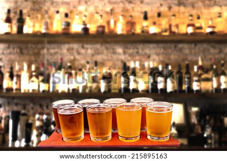 Beer flight of eight sampling glasses of craft beer on a bar countertop. - stock photo