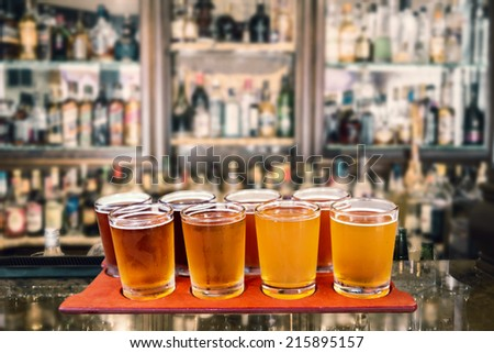 Beer flight of eight sampling glasses of craft beer on a serving board in a bar. - stock photo