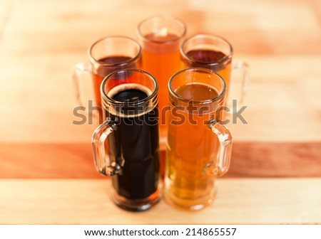 Beer flight of five sampling mugs of light and dark craft beer. Circle of little mugs with handles to the outside. - stock photo