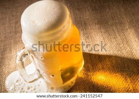 Beer foam overflowing from mason jar. - stock photo