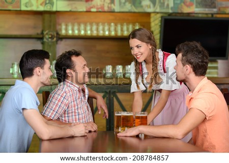 Beer for gentlemen. Beautiful young waitress serving beer while three men sitting at the table in beer pub - stock photo