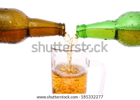 Beer from a bottle poured into a glass - stock photo