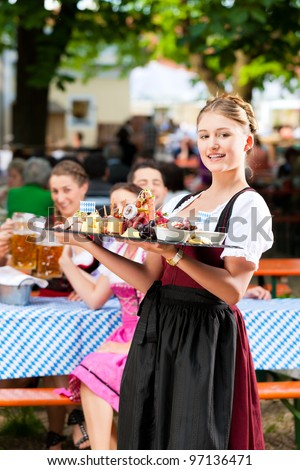 Beer garden restaurant in Bavaria, Germany - beer and snacks are served, the waitress also wears traditional costume - stock photo