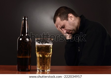 Beer glass and bottle, alcoholic in despair - stock photo