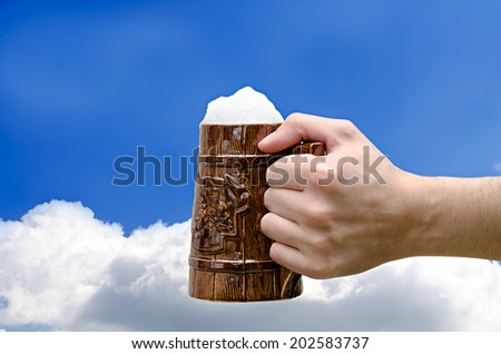 beer glass in a hand against the sky - stock photo