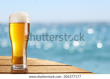 Beer glass on a blurred background of the sea. - stock photo
