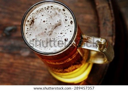 beer glass on wooden barrel - stock photo