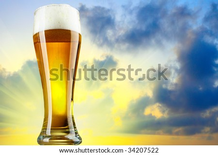 Beer glass with froth and sundown in the background - stock photo