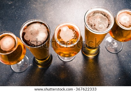 Beer glasses on dark table - stock photo
