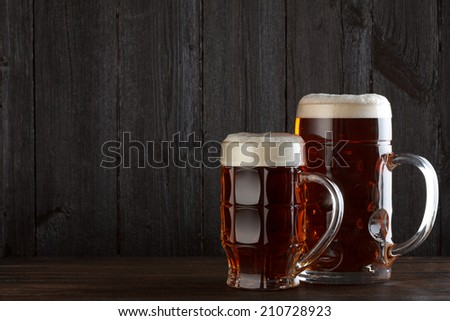 Beer glasses on table, dark wooden background with copy space - stock photo