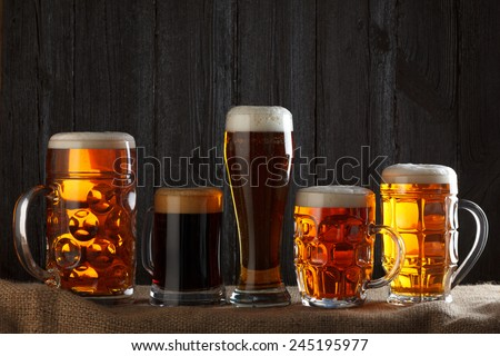Beer glasses with lager, dark lager, brown ale, malt and stout beer on table, dark wooden background - stock photo