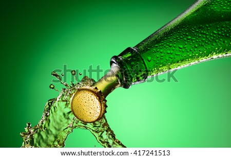 Beer green bottle neck and cap macro shot. Bottle opening with exploding and splashing - stock photo