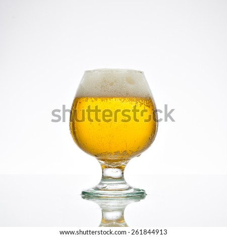 Beer  in a glass on glossy surface  with drops isolated on background - stock photo