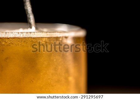 Beer in glass on black background - stock photo