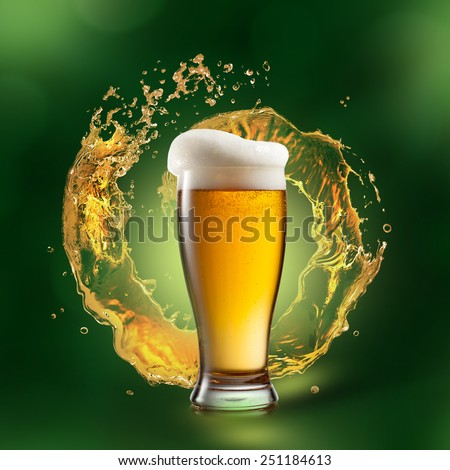 Beer in glass with splash on green natural background - stock photo