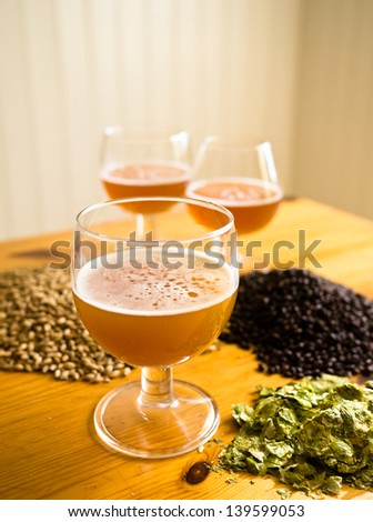 Beer in glasses, hops and malt displayed on table - portrait view - stock photo