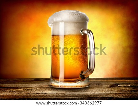 Beer in mug on wooden table and yellow background - stock photo