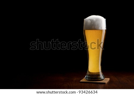 Beer into glass on a black and wooden table - stock photo
