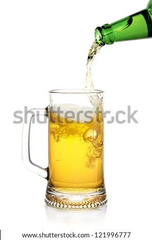 Beer is poured from a green bottle into a glass, isolated on white - stock photo