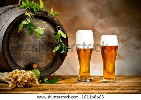 Beer keg with glasses of beer and blur background - stock photo