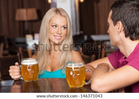 Beer lovers. Young cheerful couple drinking beer at the bar - stock photo