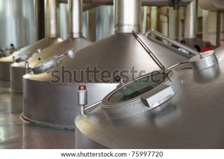 Beer-making tanks in industrial building - stock photo