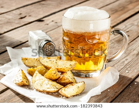 Beer mug and potato wedges on rustic vintage planked wood table - snack bar or pub menu - stock photo