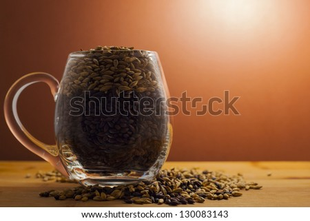 Beer mug filled with dark and pale malts - stock photo