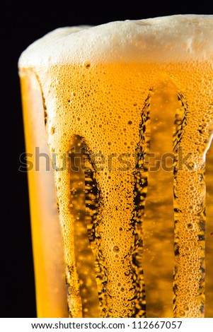 Beer mug with froth over black background - stock photo