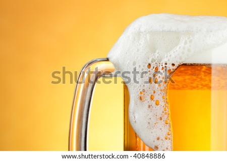 Beer mug with froth over yellow background - stock photo