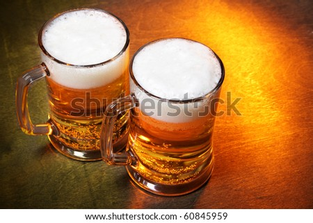 Beer mugs close up on wooden table - stock photo
