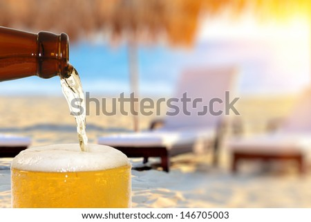 Beer on the beach background - stock photo