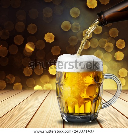 Beer Pour into Glass on Wood Table - stock photo