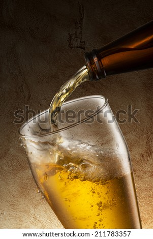 Beer pour into glass with grunge background - stock photo