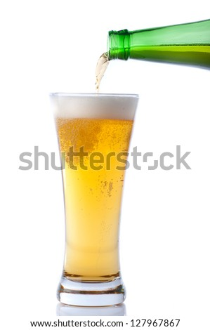 Beer pouring from bottle into glass on white - stock photo