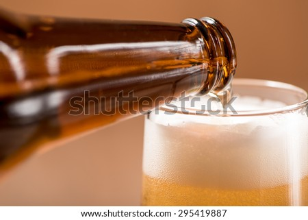 beer pouring from bottle on wood background - stock photo