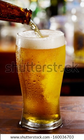 beer pouring into glass in a bar - stock photo