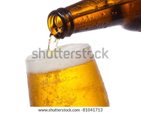 Beer pouring into glass on white background - stock photo