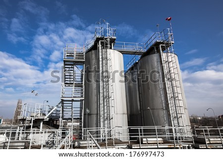 beer processing and storage silos against blue sky - stock photo
