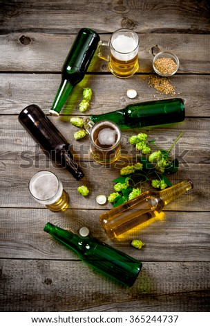 Beer set. Bottles and glasses of beer, malt and green hops on a wooden table. Top view - stock photo