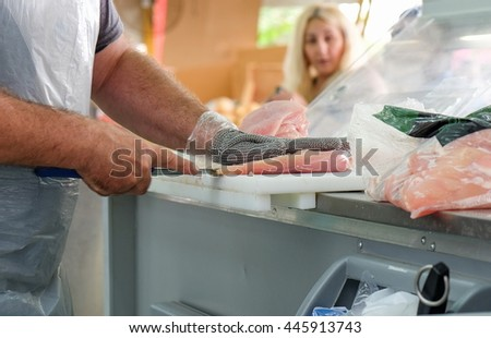 BEER-SHEVA, ISRAEL - JUNE 28, 2016: The hands of a butcher cutting slices of raw chicken breast - stock photo