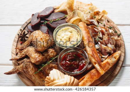Beer snacks mix on wooden board with two sauces top view. Flat lay of closeup tasty set of grilled chicken wings, chips, meat and cheese on white wooden background - stock photo