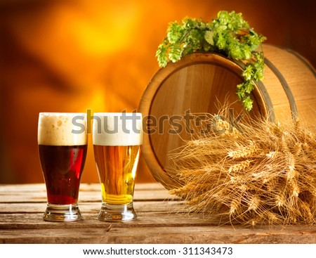 Beer. Still life with Vintage beer barrel and two glasses of dark and light beer. Fresh amber beer concept. Green hop and gold wheat on wooden table. Ingredients for brewery. Brewing traditions - stock photo