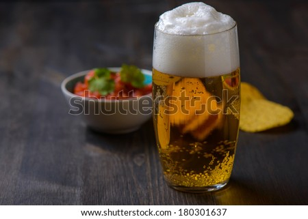 Beer with nachos and salsa in the background - stock photo
